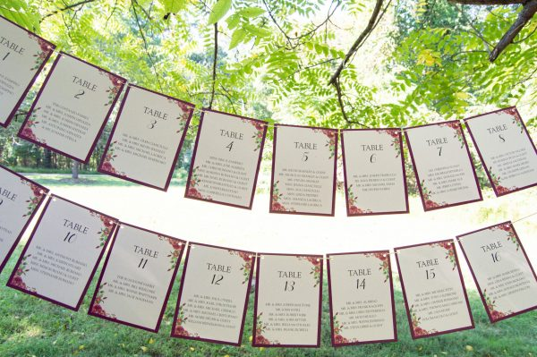 Rustic hangin seating chart with wine cardstock backing and rose illustration The Brownstone Wedding NJ