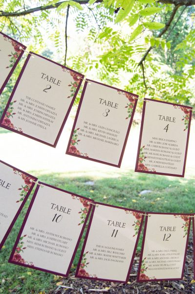 Rustic hangin seating chart with wine cardstock backing and rose illustration